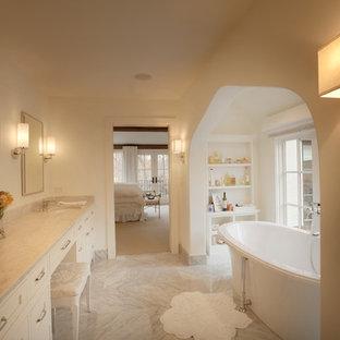 Modelo de cuarto de baño tradicional con lavabo bajoencimera, armarios con paneles empotrados, puertas de armario blancas y bañera exenta