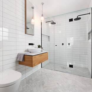 Photo of a mid-sized contemporary master bathroom in Melbourne with white tile, white walls, marble benchtops, a curbless shower, a wall-mount toilet and a vessel sink.