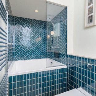 Modelo de cuarto de baño actual, pequeño, con bañera japonesa, combinación de ducha y bañera, sanitario de pared, baldosas y/o azulejos azules, baldosas y/o azulejos de cerámica, paredes azules, suelo de baldosas de porcelana, encimera de piedra caliza, suelo beige y encimeras blancas
