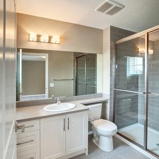 Идея дизайна: маленькая главная ванная комната в современном стиле с фасадами в стиле шейкер, белыми фасадами, столешницей из ламината, раздельным унитазом, серой плиткой, керамической плиткой, бежевыми стенами, полом из винила и накладной раковиной