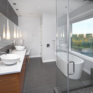 Example of a trendy freestanding bathtub design in Edmonton with a vessel sink