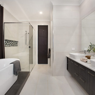 This is an example of an expansive contemporary master bathroom in Gold Coast - Tweed with engineered quartz benchtops, flat-panel cabinets, dark wood cabinets, a freestanding tub, a corner shower, beige tile, porcelain tile, porcelain floors, a vessel sink, beige floor, a hinged shower door and white benchtops.