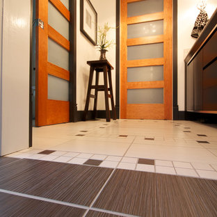 Inspiration for a mid-sized contemporary master white tile and porcelain tile porcelain floor and white floor bathroom remodel in Montreal with flat-panel cabinets, black cabinets, a one-piece toilet, white walls, an undermount sink, solid surface countertops and a hinged shower door