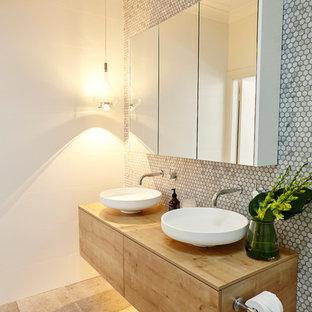 Modern inredning av ett mellanstort brun brunt en-suite badrum, med ett fristående handfat, skåp i mellenmörkt trä, mosaik, en toalettstol med hel cisternkåpa, grå kakel, vita väggar, klinkergolv i keramik, träbänkskiva, släta luckor, en dusch i en alkov och med dusch som är öppen