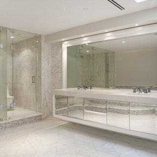 Idéer för stora funkis en-suite badrum, med ett platsbyggt badkar, grå kakel, beige väggar, luckor med glaspanel, en hörndusch, en toalettstol med separat cisternkåpa, marmorkakel, marmorgolv, ett integrerad handfat, bänkskiva i kvarts, grå skåp, vitt golv och dusch med gångjärnsdörr