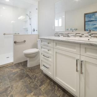 Immagine di una stanza da bagno padronale chic di medie dimensioni con ante in stile shaker, ante bianche, zona vasca/doccia separata, WC monopezzo, piastrelle multicolore, piastrelle di vetro, pareti grigie, pavimento in vinile, lavabo da incasso e top in laminato
