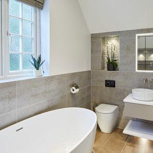 Foto di una stanza da bagno padronale industriale di medie dimensioni con piastrelle grigie, piastrelle in gres porcellanato, ante lisce, ante grigie, vasca freestanding, pareti bianche, lavabo a bacinella, pavimento marrone e top bianco