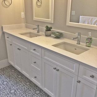 Diseño de cuarto de baño principal, campestre, con armarios con paneles lisos, puertas de armario blancas, sanitario de una pieza, baldosas y/o azulejos blancos, paredes beige, suelo vinílico, lavabo bajoencimera, encimera de cuarzo compacto, suelo multicolor y encimeras blancas