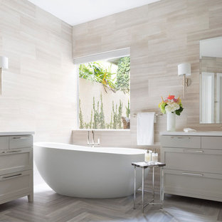Inspiration for a large transitional master bathroom in Miami with an integrated sink, shaker cabinets, grey cabinets, quartzite benchtops, a freestanding tub, beige tile, limestone floors, limestone and grey floor.