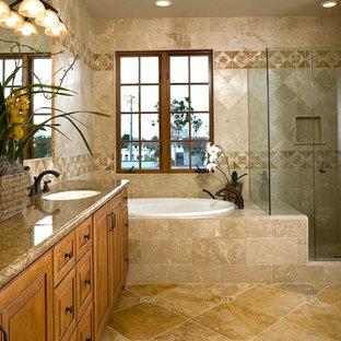 Photo of a large mediterranean ensuite bathroom in Santa Barbara with a submerged sink, raised-panel cabinets, medium wood cabinets, granite worktops, a corner shower, beige tiles, travertine flooring, a built-in bath and travertine tiles.
