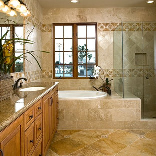 Photo of a large mediterranean ensuite bathroom in Santa Barbara with a submerged sink, raised-panel cabinets, medium wood cabinets, granite worktops, a corner shower, beige tiles, travertine flooring, a built-in bath and travertine tiles.
