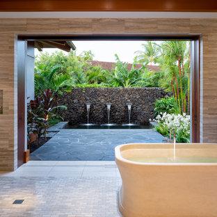 Immagine di una stanza da bagno padronale tropicale con vasca freestanding, doccia a filo pavimento e piastrelle grigie