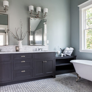 Example of a classic claw-foot bathtub design in Portland with shaker cabinets