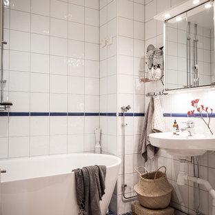 Idéer för att renovera ett nordiskt badrum, med ett fristående badkar, vit kakel, ett väggmonterat handfat och blått golv