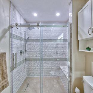 Modelo de cuarto de baño principal, tradicional renovado, pequeño, con armarios estilo shaker, puertas de armario blancas, ducha empotrada, sanitario de dos piezas, baldosas y/o azulejos blancos, baldosas y/o azulejos azules, baldosas y/o azulejos de cerámica, lavabo bajoencimera, suelo gris, ducha con puerta corredera, paredes beige, suelo de cemento, encimera de granito y encimeras multicolor