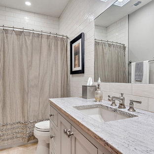 Inspiration for a medium sized mediterranean family bathroom in Austin with shaker cabinets, grey cabinets, an alcove shower, a two-piece toilet, white tiles, ceramic tiles, grey walls, travertine flooring, a submerged sink, granite worktops, beige floors, an open shower, multi-coloured worktops and an alcove bath.