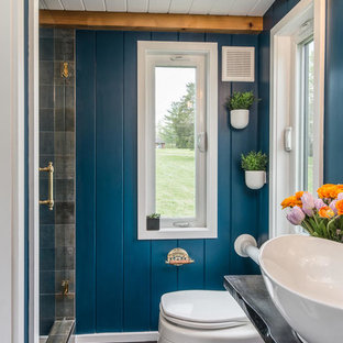 Example of an urban 3/4 gray tile dark wood floor and brown floor alcove shower design in Nashville with a one-piece toilet, blue walls, a vessel sink, a hinged shower door and black countertops
