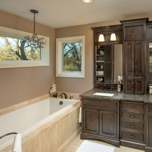 Inspiration for a timeless drop-in bathtub remodel in Columbus with an undermount sink, shaker cabinets, dark wood cabinets and beige walls