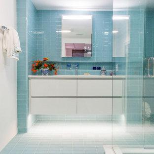 Immagine di una stanza da bagno con doccia minimalista di medie dimensioni con ante lisce, ante bianche, doccia ad angolo, piastrelle blu, piastrelle di vetro, pareti bianche, pavimento con piastrelle in ceramica, lavabo sottopiano, top in superficie solida, pavimento blu, porta doccia a battente e top bianco