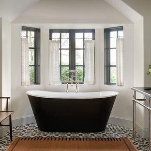 Diseño de cuarto de baño mediterráneo con bañera exenta, paredes blancas, lavabo bajoencimera, suelo multicolor y encimeras negras