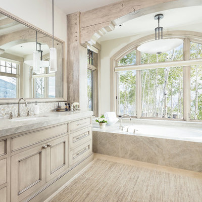 Bathroom - rustic master beige tile beige floor bathroom idea in Salt Lake City with recessed-panel cabinets, beige cabinets, an undermount tub, white walls, an undermount sink and gray countertops