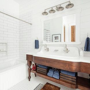 Bild på ett lantligt vit vitt badrum, med möbel-liknande, skåp i mörkt trä, vit kakel, vita väggar, ett avlångt handfat och vitt golv