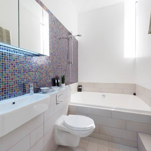 Medium sized contemporary ensuite bathroom in London with a built-in bath, a shower/bath combination, a wall mounted toilet, mosaic tiles, white walls, multi-coloured tiles, a wall-mounted sink and beige floors.
