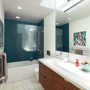 Стильный дизайн: маленькая ванная комната в стиле ретро с плоскими фасадами, фасадами цвета дерева среднего тона, ванной в нише, душем над ванной, унитазом-моноблоком, синей плиткой, плиткой из листового стекла, белыми стенами, полом из керамогранита, душевой кабиной, раковиной с несколькими смесителями, столешницей из искусственного кварца, бежевым полом, душем с распашными дверями и белой столешницей - последний тренд