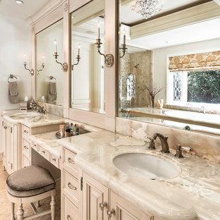 Foto di una stanza da bagno padronale chic di medie dimensioni con lavabo sottopiano, consolle stile comò, top in onice, vasca sottopiano, piastrelle gialle, piastrelle in pietra, pareti beige e pavimento in pietra calcarea