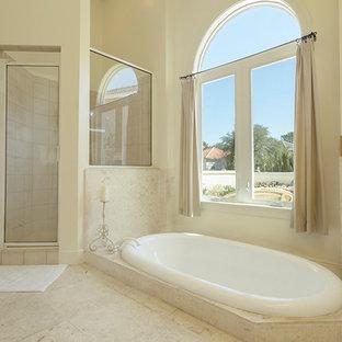 На фото: большая главная ванная комната в современном стиле с плоскими фасадами, бежевыми фасадами, ванной на ножках, угловым душем, унитазом-моноблоком, бежевой плиткой, плиткой из известняка, бежевыми стенами, полом из известняка, раковиной с пьедесталом и столешницей из известняка с