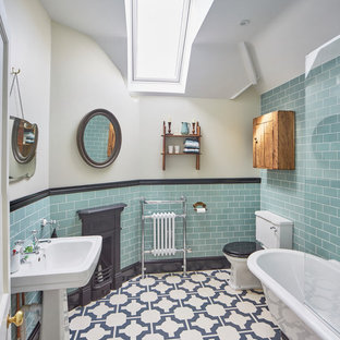 This is an example of a traditional ensuite bathroom in Oxfordshire with a claw-foot bath, a two-piece toilet, blue tiles, metro tiles, white walls, a pedestal sink and multi-coloured floors.