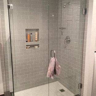 Aménagement d'une salle de bain contemporaine de taille moyenne avec un carrelage gris, un carrelage métro, un mur rouge, un sol en carrelage de porcelaine, un sol gris et une cabine de douche à porte battante.