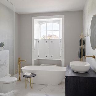 Imagen de cuarto de baño principal, moderno, con armarios con paneles lisos, puertas de armario de madera en tonos medios, bañera exenta, ducha abierta, sanitario de pared, baldosas y/o azulejos blancas y negros, baldosas y/o azulejos de porcelana, paredes grises, suelo de baldosas de porcelana, encimera de madera, suelo blanco, ducha abierta y encimeras azules