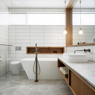 Design ideas for a midcentury bathroom in Melbourne with a freestanding tub, white tile, marble benchtops, flat-panel cabinets, medium wood cabinets, a vessel sink, grey floor and white benchtops.