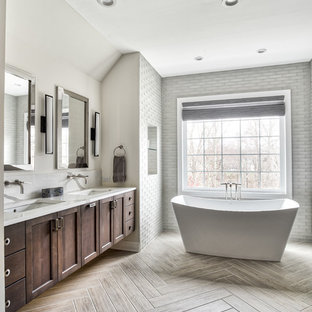 На фото: огромная главная ванная комната в стиле современная классика с фасадами в стиле шейкер, темными деревянными фасадами, отдельно стоящей ванной, душем в нише, серой плиткой, стеклянной плиткой, бежевыми стенами, врезной раковиной, столешницей из искусственного кварца, душем с распашными дверями и белой столешницей