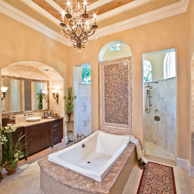Example of a large classic master beige tile and stone tile beige floor bathroom design in Houston with a vessel sink, dark wood cabinets, a one-piece toilet, recessed-panel cabinets and beige walls