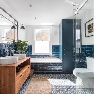 Foto på ett mellanstort vintage brun badrum för barn, med släta luckor, skåp i mellenmörkt trä, ett platsbyggt badkar, en hörndusch, en toalettstol med separat cisternkåpa, blå kakel, tunnelbanekakel, vita väggar, cementgolv, ett fristående handfat, träbänkskiva och flerfärgat golv