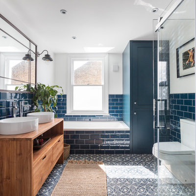 Mid-sized transitional kids' blue tile and subway tile cement tile floor and multicolored floor bathroom photo in London with flat-panel cabinets, medium tone wood cabinets, a two-piece toilet, white walls, a vessel sink, wood countertops and brown countertops