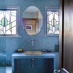 Photo of a mediterranean bathroom in London with a built-in sink, blue tiles and blue walls.