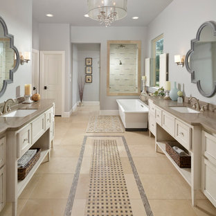 Large tuscan master porcelain floor and beige floor freestanding bathtub photo in Houston with an undermount sink, white cabinets, gray walls, recessed-panel cabinets and gray countertops