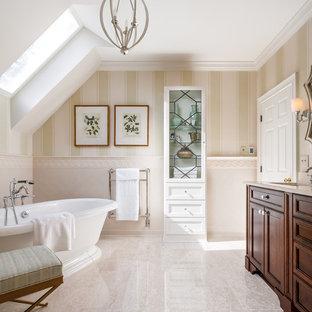 Ispirazione per una stanza da bagno tradizionale con consolle stile comò, ante in legno bruno, vasca freestanding, piastrelle beige, pareti beige, lavabo sottopiano e pavimento beige