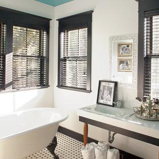 Idée de décoration pour une salle de bain victorienne avec une baignoire sur pieds, un carrelage noir et blanc, un lavabo intégré et un sol multicolore.