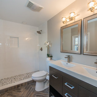 Small transitional master gray tile and ceramic tile ceramic floor and brown floor bathroom photo in New York with flat-panel cabinets, dark wood cabinets, a two-piece toilet, gray walls, an integrated sink and quartz countertops