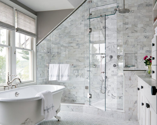 Claw foot tub white tile subway tile gray walls and marble floors