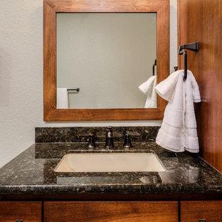 Foto di una piccola stanza da bagno con doccia stile rurale con ante in stile shaker, ante in legno scuro, doccia alcova, WC monopezzo, piastrelle grigie, piastrelle in gres porcellanato, pareti blu, pavimento in gres porcellanato, lavabo sottopiano, top in granito, pavimento beige, porta doccia a battente, top nero, panca da doccia, un lavabo e mobile bagno incassato