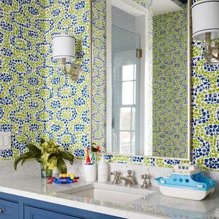 Diseño de cuarto de baño infantil, costero, de tamaño medio, con armarios con paneles lisos, puertas de armario azules, paredes multicolor, lavabo bajoencimera y encimera de esteatita