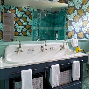 Modelo de cuarto de baño infantil, clásico renovado, grande, con armarios abiertos, puertas de armario azules, paredes multicolor, suelo de baldosas de cerámica, lavabo de seno grande, encimera de acrílico, suelo verde y encimeras blancas