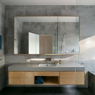 This is an example of a contemporary bathroom in Melbourne with flat-panel cabinets, medium wood cabinets, a drop-in tub, gray tile, grey walls, an undermount sink, black floor and grey benchtops.