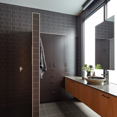 Mid-sized trendy master brown tile and ceramic tile ceramic tile bathroom photo in Melbourne with a vessel sink, furniture-like cabinets, dark wood cabinets and brown walls