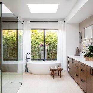 Modern inredning av ett stort vit vitt en-suite badrum, med släta luckor, skåp i mörkt trä, ett fristående badkar, en kantlös dusch, vita väggar, kalkstensgolv, bänkskiva i kvarts, vitt golv och dusch med gångjärnsdörr